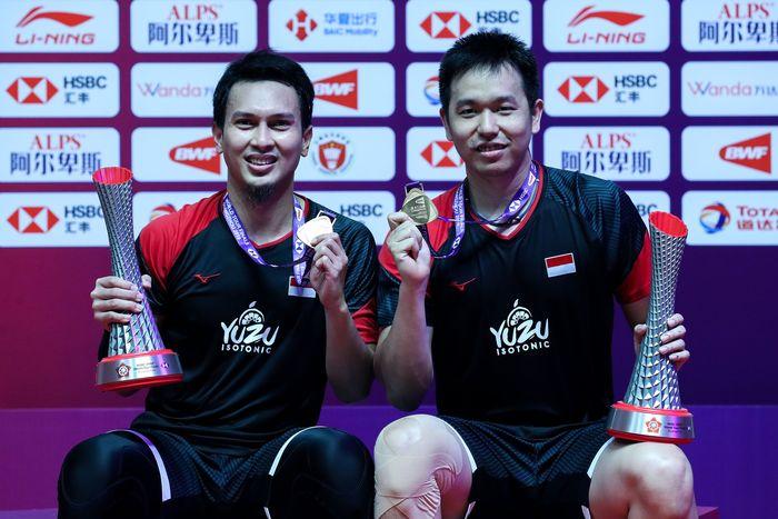 Hendra Setiawan dan Muhammad Ahsan menunjukkan trofi dan medali BWF World Tour Finals 2019. Mereka menang atasHiroyuku Endo/Yuta Watanabe. The Daddies menang dua gim langsung 24-22 dan 21-19. Istimewa/PBSI.