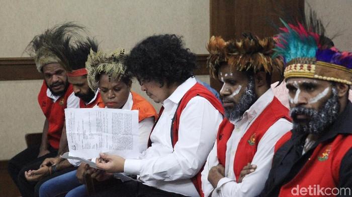 Lima tersangka pengibar bendera bintang kejora memakai topi adat khas Papua bernama kari-kari saat menjalani sidang perdana.