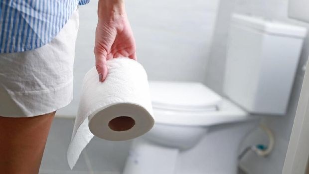 Woman holds toilet paper roll in front of toilet bowl.