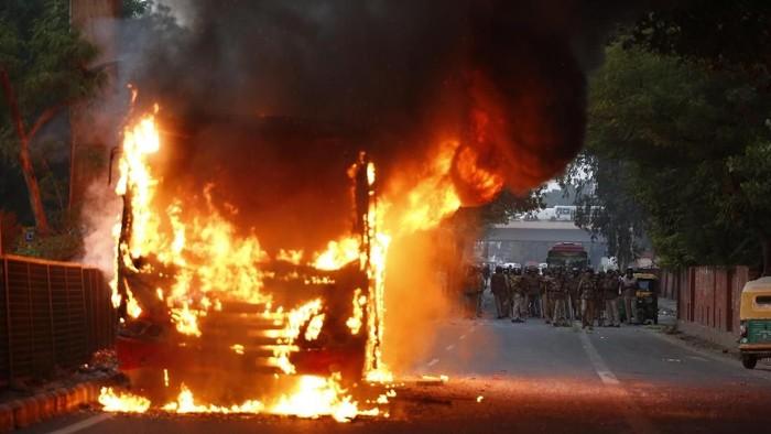 Sebuah bus dibakar dalam bentrokan di New Delhi (AP Photo)