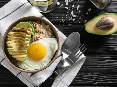 Bowl with delicious oatmeal, egg and avocado on wooden table