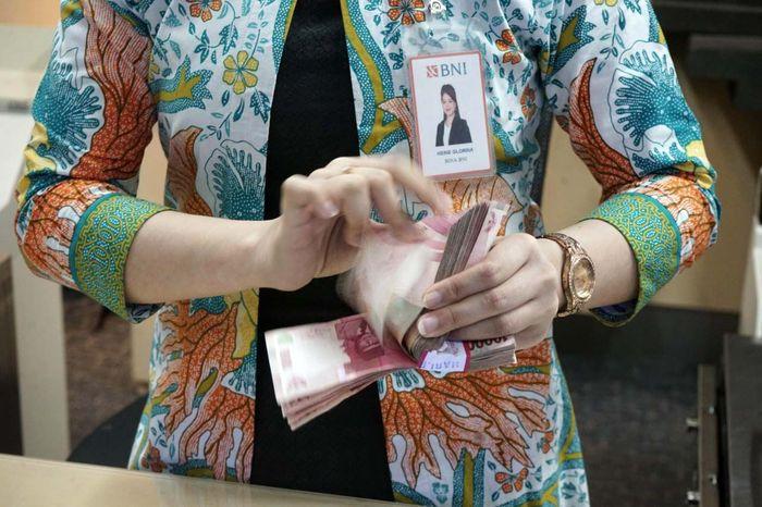Petugas teller PT Bank Negara Indonesia (Persero) Tbk atau BNI sedang menghitung uang di kantor BNI Jakarta, Kamis (19/120).