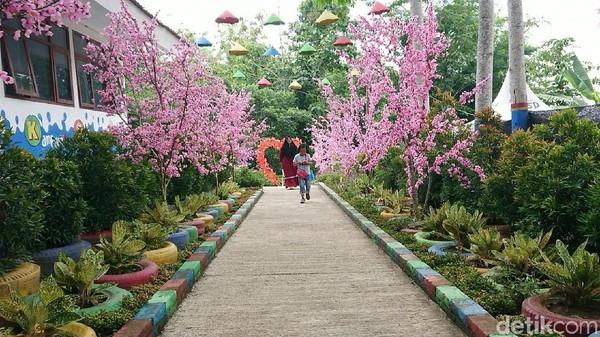Memasuki kawasan wisata Kampung Susu, pengunjung akan disambut oleh spot selfie berupa aneka bunga sakura buatan. Kampung Susu ini berada di Desa Sidem, Kecamatan Gondang, Tulungagung. (Adhar Muttaqin/detikcom)