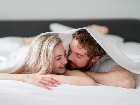 Loving young couple in bed looking very affectionate towards each other - relationship concepts