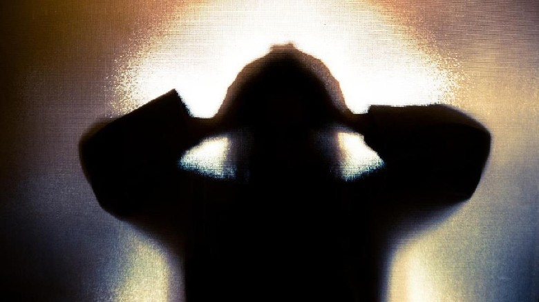 Colour backlit image of the silhouette of a woman with her hands on her head in a gesture of despair. The silhouette is distorted, and the arms elongated, giving an alien-like quality. The image is sinister and foreboding, with an element of horror. It is as if the woman is trying to escape from behind the glass. Horizontal image with copy space.