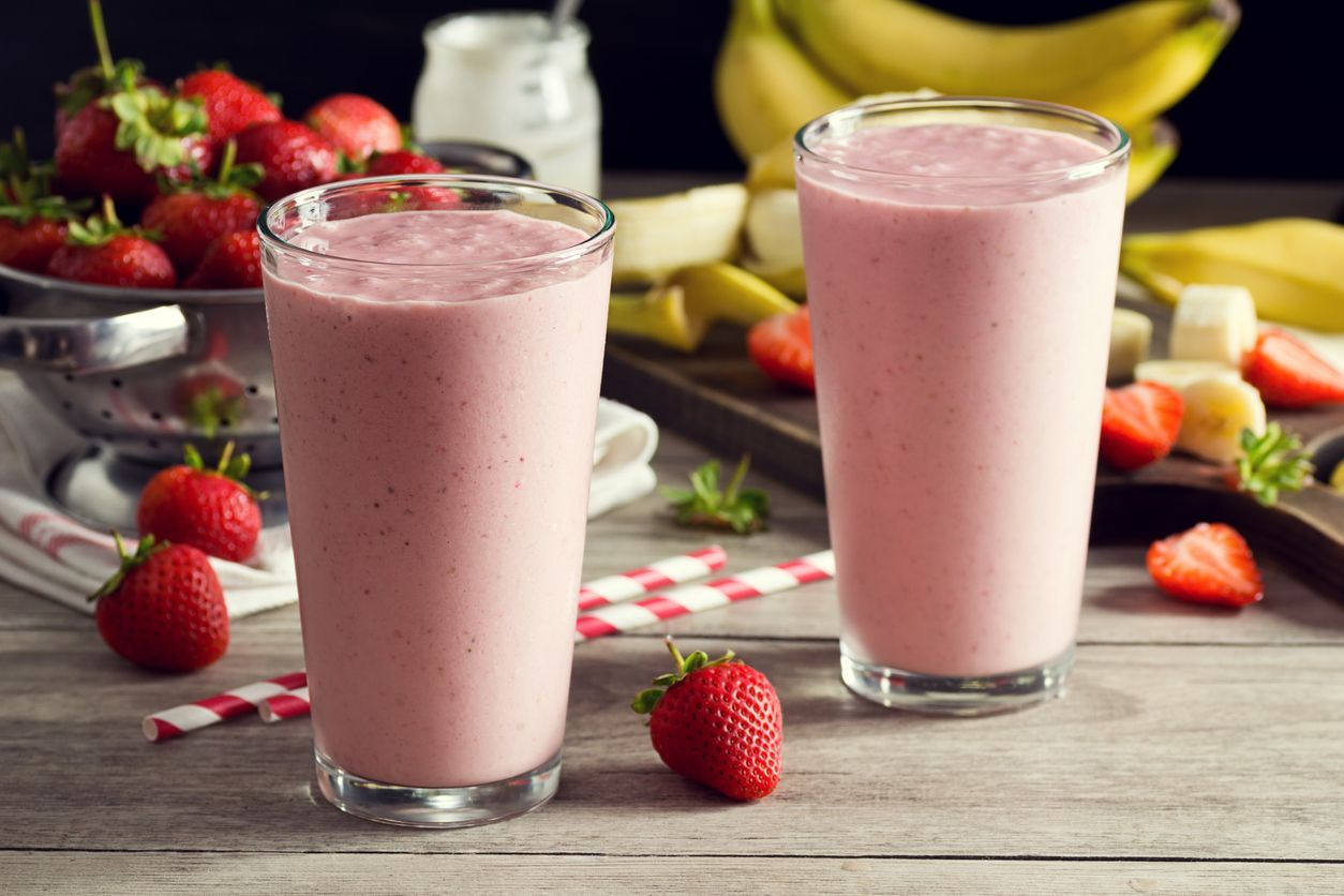 Two cold strawberry banana yogurt smoothies in pint glasses with striped straws. The berries and bananas are in the background in a colander and on a cutting board. A jar of yogurt is also in the background. Everything is on a faded wood picnic table.