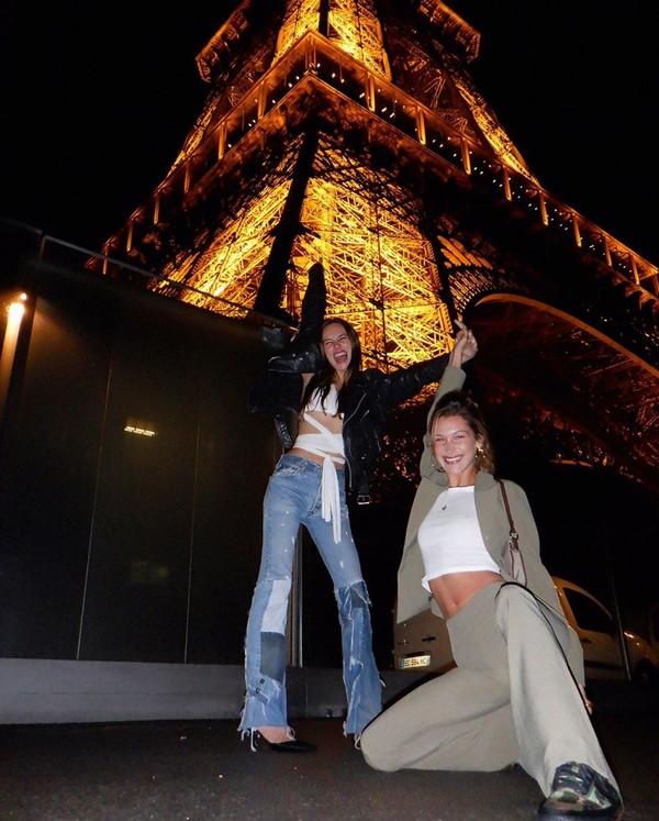Model Bella Hadid tampak ceria berfoto dengan latar Menara Eiffel di malam hari. (Foto: instagram @bellahadid)