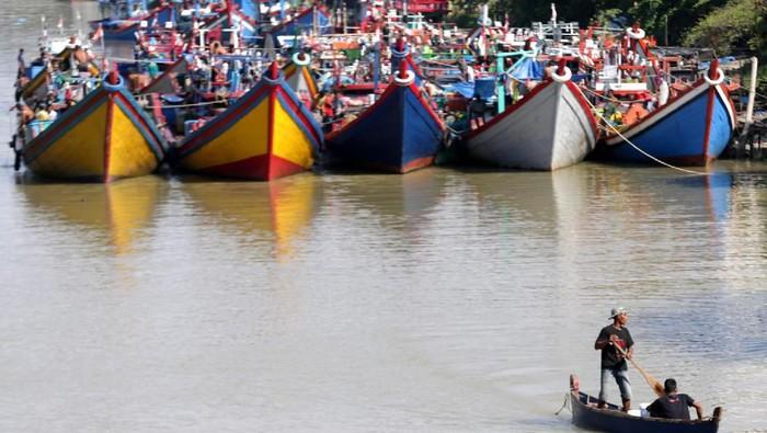 Nelayan membenahi jaring diantara kapal dan perahu yang ditambatkan di Daerah Aliran Sungai (DAS) Krueng Aceh, Peunayong, Banda Aceh, Aceh, Rabu (25/12/2019).  Nelayan Aceh yang diatur dalam hukum adat laut telah menyepakati setiap tanggal 26 Desember wajib libur guna mengenang bencana tsunami dan mendoakan keluarga yang menjadi korban pada peristiwa 15 tahun lalu itu. ANTARA FOTO/Irwansyah Putra/ama.