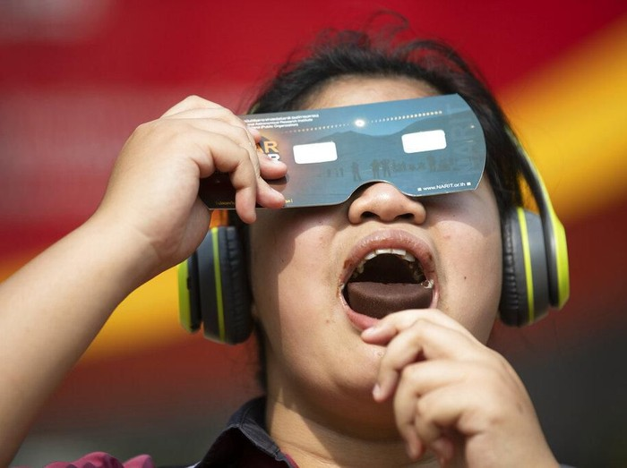 A student holds a special filter to observe a solar eclipse while eating an ice cream treat at a school in Bangkok, Thailand, Thursday, Dec. 26, 2019. (AP Photo/Sakchai Lalit)