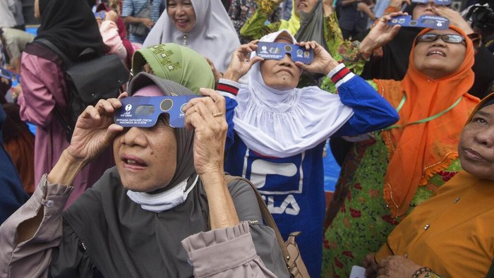 Muslim women watch a solar eclipse through special glasses at the campus of the Faculty of Astronomy of Muhammadiah University of North Sumatra (UMSU) in Medan, Indonesia, Thursday, Dec. 26, 2019. People along a swath of southern Asia gazed at the sky in marvel on Thursday at a