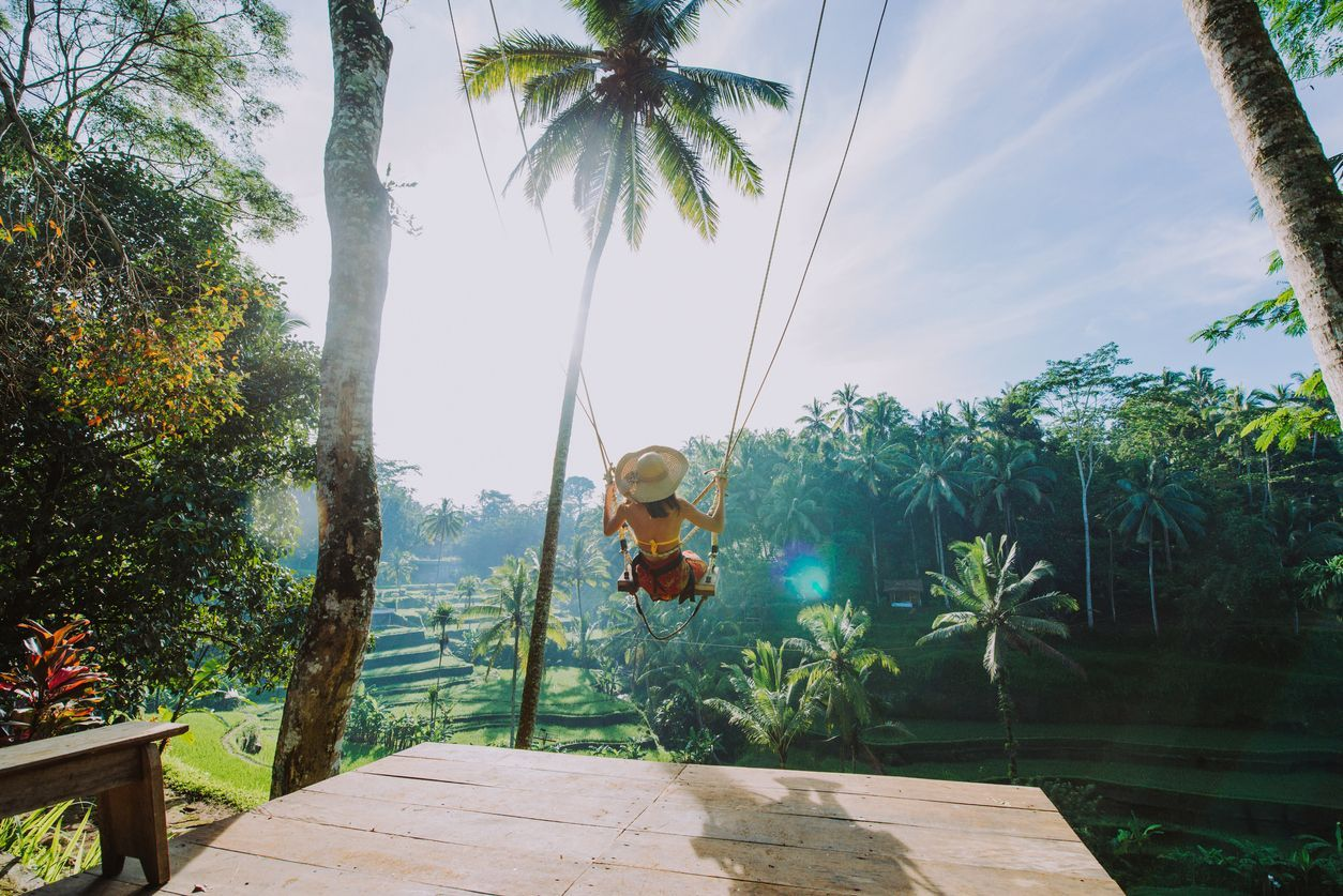 Beautiful girl visiting the Bali rice fields in tegalalang, ubud. Using a swing over the jungle. Concept about people, wanderlust traveling and tourism lifestyle