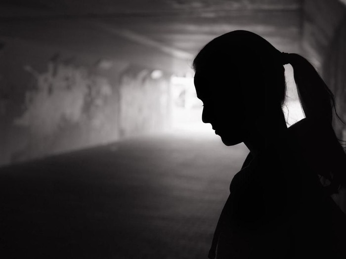 Depressed sad young female standing in a dark tunnel