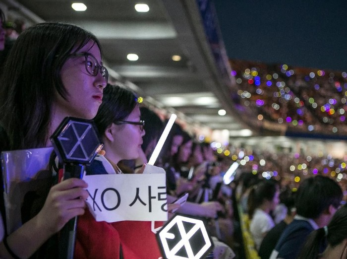 SUWON, SOUTH KOREA - JUNE 18:  A South Korean fan (L) of a boy band, Exo, (not shown) holds a banner as a K-Pop band perform on stage on June 18, 2016 in Suwon, South Korea.The particular concert was organized by the city government of Suwon, commemorating the 220th anniversary of Suwon-Hwaseong Fortress, a UNESCO heritage site. It featured 25 K-Pop idol groups and solo artists for two days: June 17 and 18, 2016, drawing more than 10,000 visitors. The South Korean government, both on a central and local level, try to boost tourism by sponsoring and directly organizing K-Pop concerts in big venues. The fans come from Korea as well as Japan, China, and Southeast Asia, as the popularity of K-pop had rapidly grown after it started in Japan in the early 2000s, and expanded its fan base to teenagers and young adults in China, Southeast Asia, and as far as Latin America.  (Photo by Jean Chung/Getty Images)