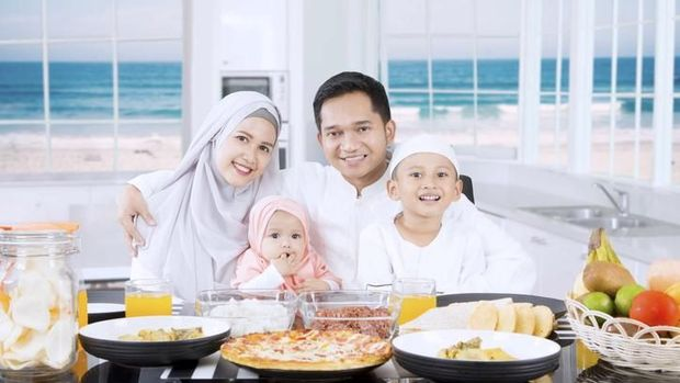 Muslim parents and cute children smiling together in the kitchen with beach background on the window