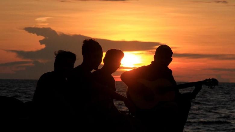 Sejumlah warga menikmati sunset atau matahari terbenam akhir tahun 2019 di Pantai Ampenan, Mataram, NTB, Selasa (31/12/2019). Taman Pantai Ampenan menjadi salah satu lokasi alternatif warga Mataram untuk melewati malam pergantian tahun. ANTARA FOTO/Ahmad Subaidi/wsj.