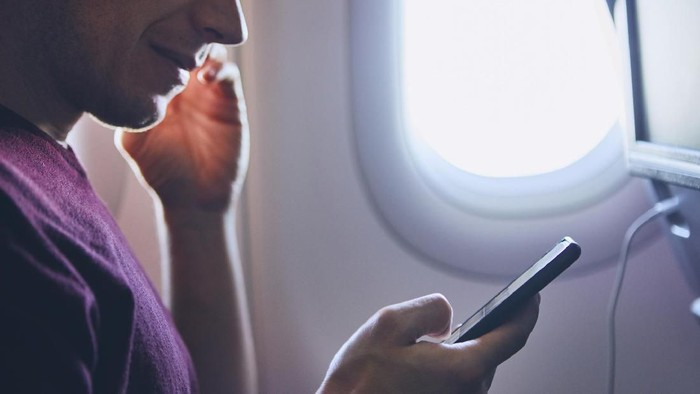 Connection during flight. Young man using mobile phone in airplane.