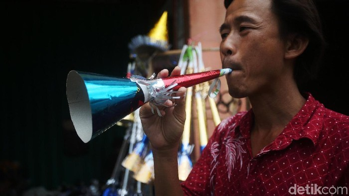 Warga membeli terompet kertas dari pedagang di Kawasan Glodok, Jakarta, Selasa (31/12/2019). Jelang malam pergantian tahun warga banyak membeli terompet. Terompet tersebut dijual dari harga Rp 5.000 hingga Rp 15.000 per buah.
