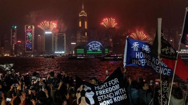 Tepatnya bukan pesta kembang api, tapi demo besar-besaran yang dilakukan oleh warga Hong Kong. Luncuran kembang api diselingi dengan pengibaran bendera dan teriakan selama perayaan tahun baru di distrik Tsim Sha Tsui, Hong Kong. (Getty Images)