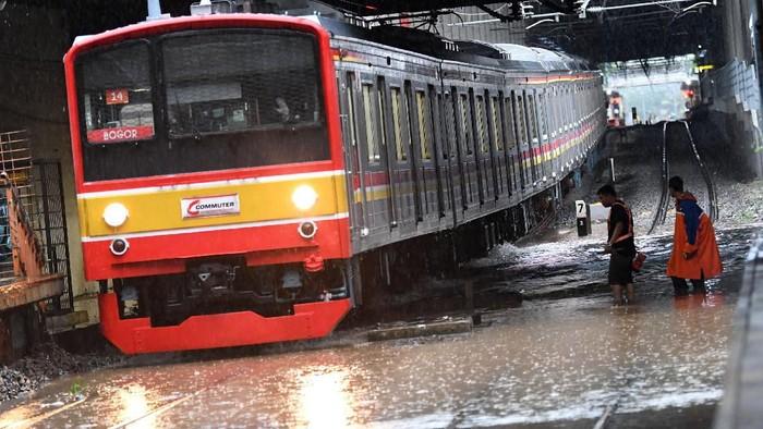 Salah satu rangkaian KRL Commuterline melintas perlahan pada jalur rel yang terendam banjir di Stasiun KA Sudirman, Menteng, Jakarta, Rabu (1/1/2020). Banjir yang menggenangi sejumlah titik pada jalur rel di Jakarta berdampak pada gangguan pelayanan sejumlah rute KRL Commuterline Jabodetabek. ANTARA FOTO/Aditya Pradana Putra/pd.   *** Local Caption ***