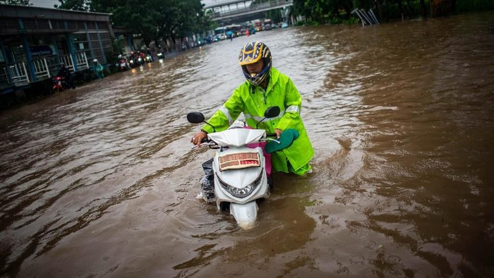 Warga mendorong motornya di dekat taksi yang terendam genangan banjir di Jalan DI Panjaitan, Cawang, Rabu (1/1/2020). Banjir tersebut disebabkan karena tingginya intensitas hujan yang mengguyur sejak Selasa (31/12/2019). ANTARA FOTO/Aprillio Akbar/foc.