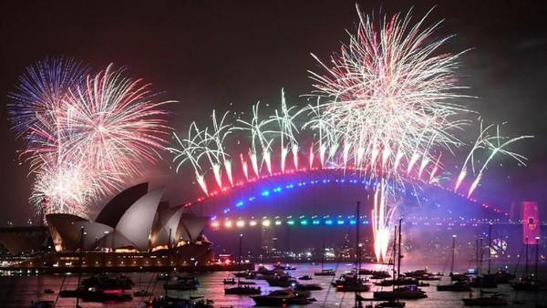 Salah satu kota favorit wisatawan di dunia juga merayakan pesta kembang api. Tepatnya di Harbour Bridge dan Opera House, Sidney, Australia. (AFP/Getty Images)