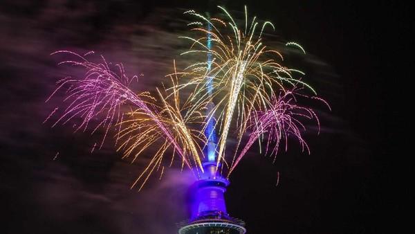 Di Auckland, New Zealand, Perayaan tahun baru dilakukan di Sky Tower. Warna merah, jingga dan hijau kembang api berbaur meluncur ke atas langit. (Getty Images)