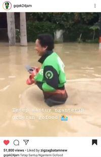 Di Tengah Banjir, Ojol Ini Tetap Semangat Antar Pesanan Makanan