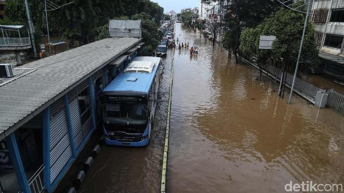 Bus TransJakarta tetap beroperasi walaupun banjir. Salah satunya di kawasan Pasar Baru. Yuk, intip foto-fotonya.
