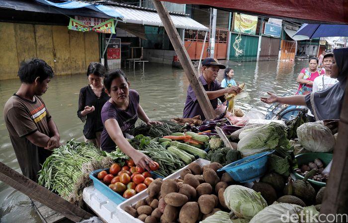 Sejumlah pedagang nampak kembali menggelar lapak dagangannya di kawasan Pasar Teluk Gong yang masih terendam banjir di Jakarta Utara, Jumat (3/1/2020).