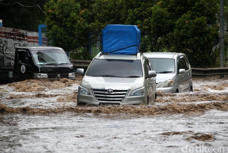 Banjir masih merendam kawasan Underpass Bekasi Barat, Bekasi. Para pengendara motor dan mobil pun nekat melintasi jalan yang terendam banjir tersebut.