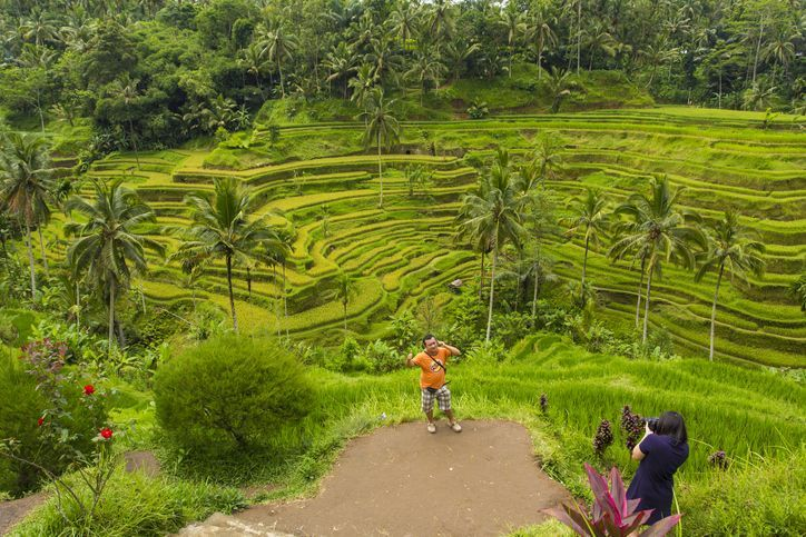 Tegalalang, Bali, Indonesia - April 19, 2013: A tourist has his photograph taken in front of traditional Balinese rice terraces