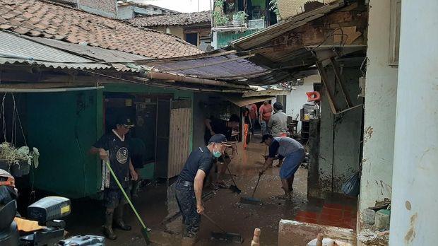 Warga dan petugas bekerja sama membersihkan lumpur sisa banjir.