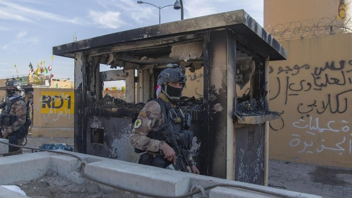 Iraqi army soldiers are deployed in front of the U.S. embassy, in Baghdad, Iraq, Wednesday, Jan. 1, 2020. Iran-backed militiamen have withdrawn from the U.S. Embassy compound in Baghdad after two days of clashes with American security forces. (AP Photo/Nasser Nasser)