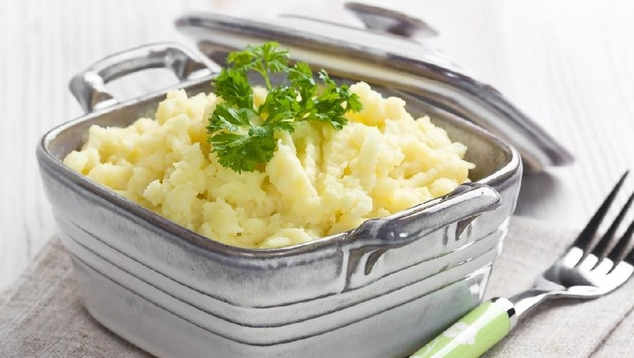 Mashed potato in ceramic bowl with fork for breakfast