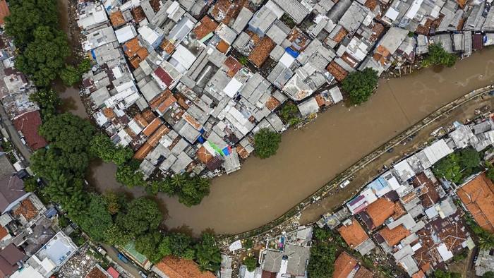 Foto udara suasana wilayah bantaran sungai Ciliwung yang belum dinormalisasi (atas) dan yang sudah dinormalisasi (bawah kanan) di kawasan Bukit Duri, Jakarta, Minggu (5/1/2020). Rencana pembangunan tanggul normalisasi atau naturalisasi yang menjadi program Gubernur Anies Baswedan hingga saat ini belum mencapai target yaitu hanya 16,19 km dari total 33,69 km dikarenakan terkendala pembebasan lahan. ANTARA FOTO/Muhammad Adimaja/aww.