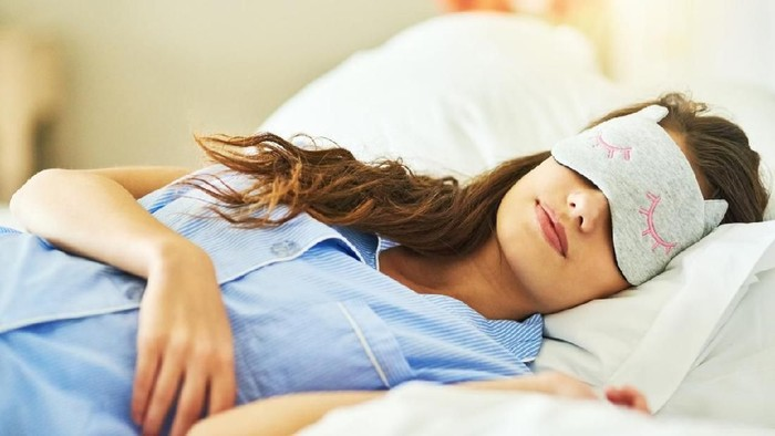 Cropped shot of an attractive young woman wearing a sleep mask while lying in bed