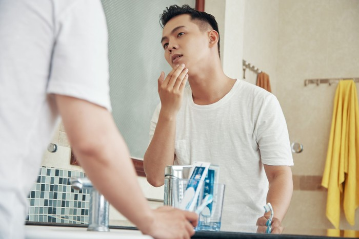 From below back view of man touching face skin looking at reflection of bathroom mirror at home