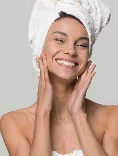Studio portrait over grey perfect woman with white towel on head after shower having toothy smile touch gently healthy shiny clean skin looking at camera, skincare and natural beauty treatment concept
