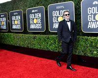 Joaquin Phoenix memakai tuksedo Stella McCartney di Golden Globes 2020.