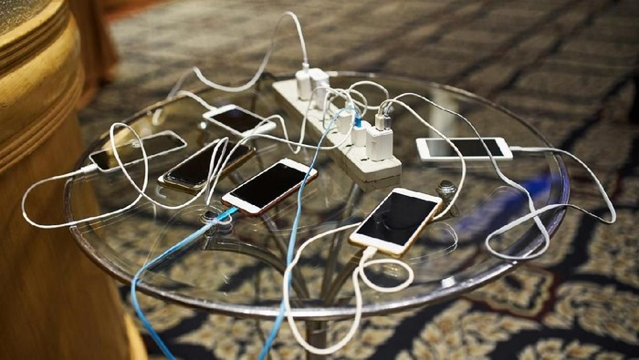 Group of smartphones charging on the glass table with sharing the same AC plug
