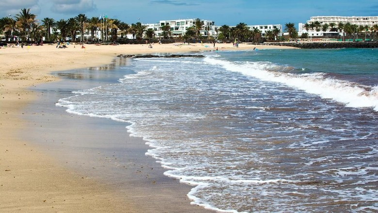 View of the beach and sea in Costa Teguise with golden sand and blue sea, Lanzarote, Spain, selective focus