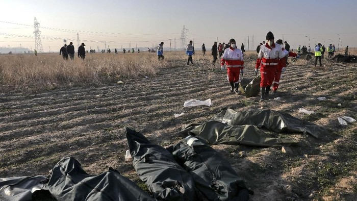 Rescue workers carry the body of a victim of an Ukrainian plane crash in Shahedshahr, southwest of the capital Tehran, Iran, Wednesday, Jan. 8, 2020. A Ukrainian airplane carrying 176 people crashed on Wednesday shortly after takeoff from Tehrans main airport, killing all onboard. (AP Photo/Ebrahim Noroozi)