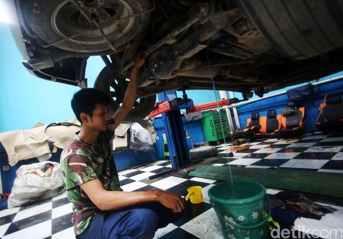 Montir memperbaiki mobil yang sempat terendam banjir, di bengkel mobil Sapta Jati Asih, Bekasi, Jawa Barat, Kamis (9/1/2020). Sebanyak 25 mobil yang terendam banjir diperbaiki di sini dengan biaya mulai Rp 2 juta hingga Rp 10 juta tergantung jenis kerusakan dan penggantian komponen.