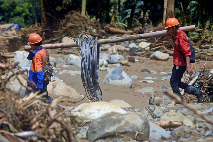 Petugas menggotong kabel melewati Sungai Ciberang untuk memperbaiki jaringan listrik yang rusak terkena banjir bandang di Kampung Jaha, Banjar Irigasi, Lebak, Banten, Kamis (9/1/2020).