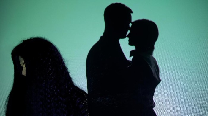 Crying girl turning head from silhouette couple kissing on background, betrayal