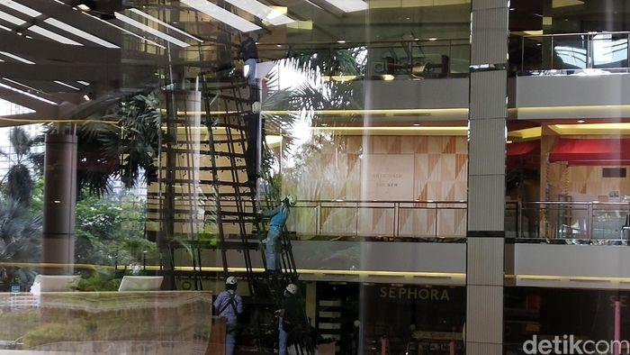 Di dalam gedung, tampak para pekerja sibuk memperbaiki tiang-tiang hiasan yang rusak akibat banjir.