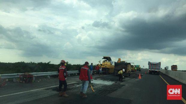 Sejumlah pekerja sedang memperbaiki jalan tol yang rusak.