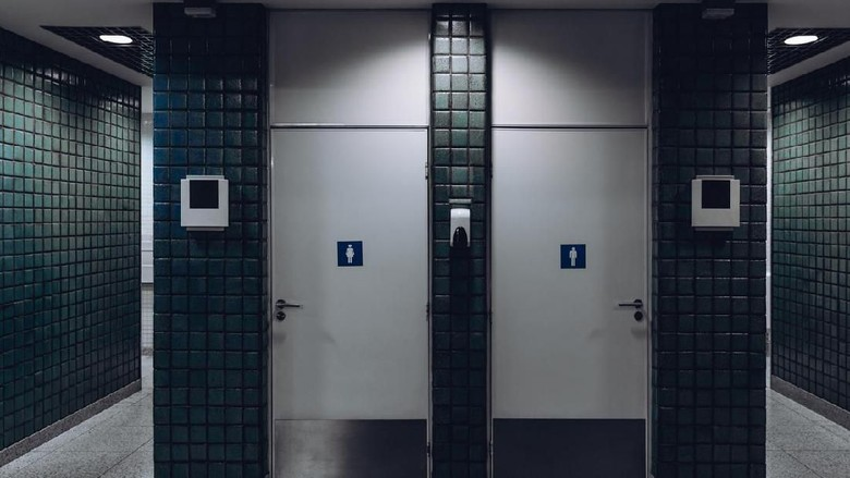 Dark public toilet entrances for men and for women in a modern airport terminal building or railway station depot, with greenish ceramic tiles on the wall: two dors and two more entrances