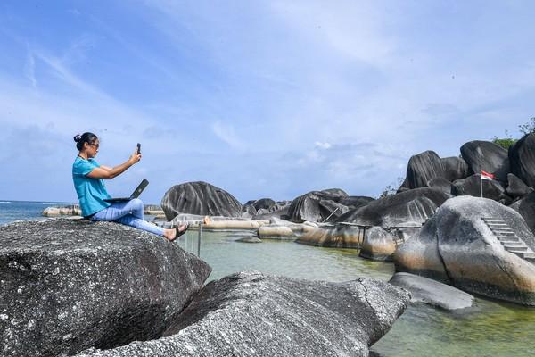 Seorang pengunjung berswafoto di atas bongkahan batu granit di Alif Stone Park, Desa Sepempang, Kabupaten Natuna, Provinsi Kepulauan Riau.
