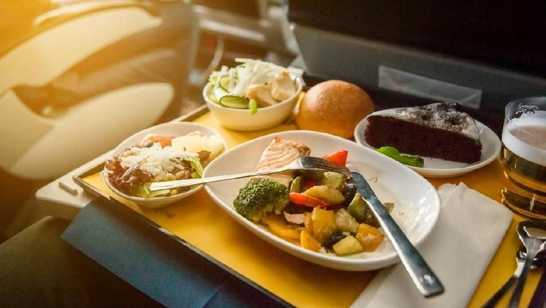 Food served on board of business class airplane on the table. Young women having a meal on board of a plane. Tray of food in the airplane. Tray of food on the plane, business class travel.